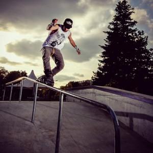 Roller boy sliding on the parapet