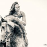 Beautiful woman in white dress and black horse portrait