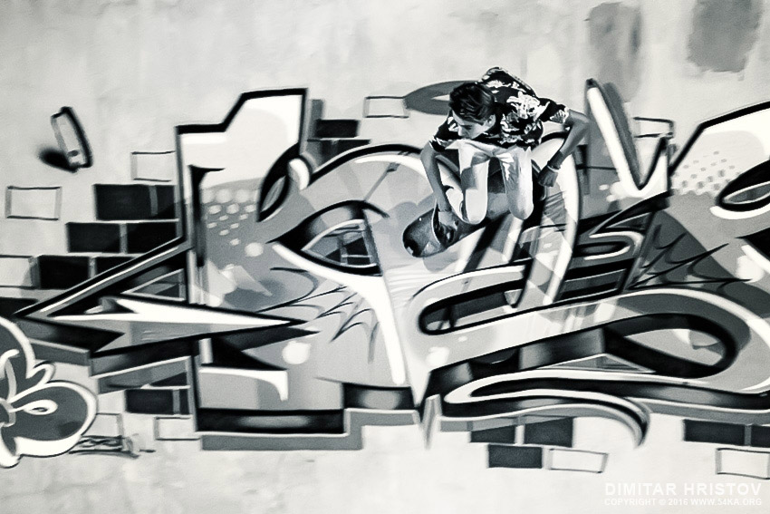 Boy riding skateboard in graffiti drawing pool photography extreme  Photo