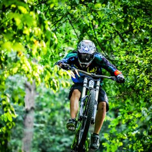 Mountainbiker rides jump in the forest