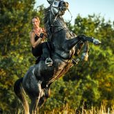 Girl riding rearing up horse – Cropped image