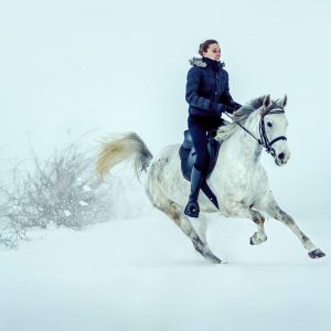 Girl rides horse in falling snow at dusk