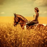 Beautiful girl riding horse at the field