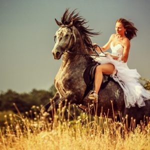 Woman riding wild horse