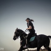 Woman riding galloping horse at dusk