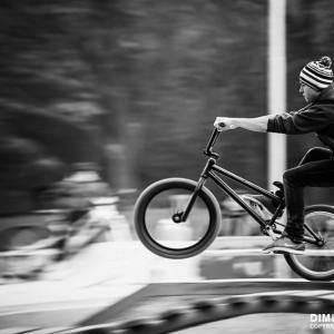 Young man riding BMX bicycle on a ramp