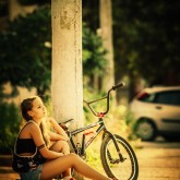 Young girl with bmx on the sunset street