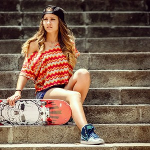 Girl with skateboard sitting on the stairs