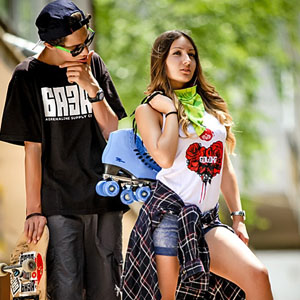 Teenage girl and boy with skateboards and roller skates outdoor portrait