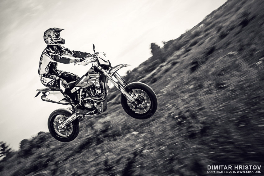 Biker making a stunt and jumps in the air photography extreme black and white  Photo