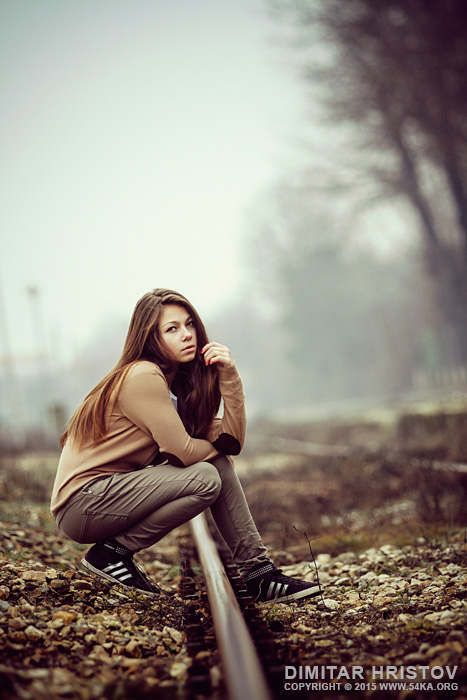 Young girl posing on the train road in the mist photography portraits daily dose  Photo