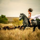 Beautiful woman wearing long white dress riding on black horse