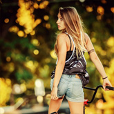 Lovely young woman riding a BMX bicycle