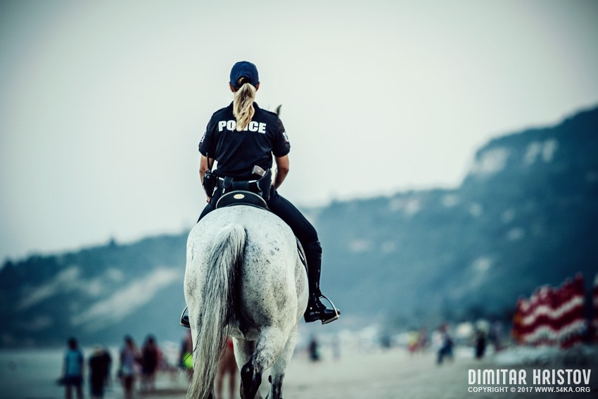 Police Officers Riding Horses On The Beach