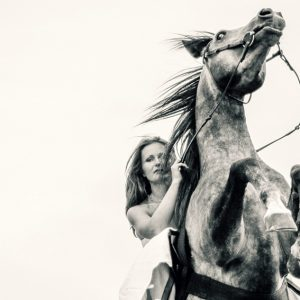 Young woman on rearing up beautiful horse