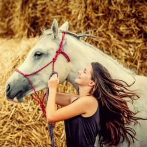 Beautiful girl with long hair with a horse