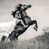 Bride in wedding dress riding a horse