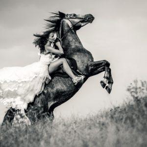 Bride in wedding dress riding a horse