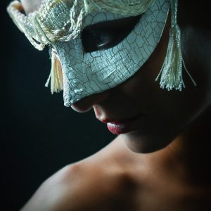 Mystery girl with white mask on black background