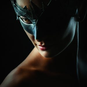 Woman with mask – Strobist portrait in the dark on black background