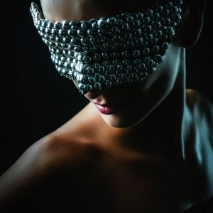 Pretty girl with conceptual silver eye carnival mask