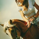 A beautiful girl is sitting on a horse and stroking it