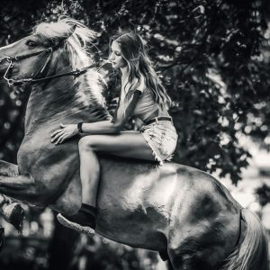 Girl rides a horse in meadow at sunset