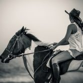Woman riding horse on the coastline
