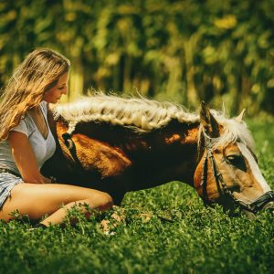 Young woman with horse on meadow